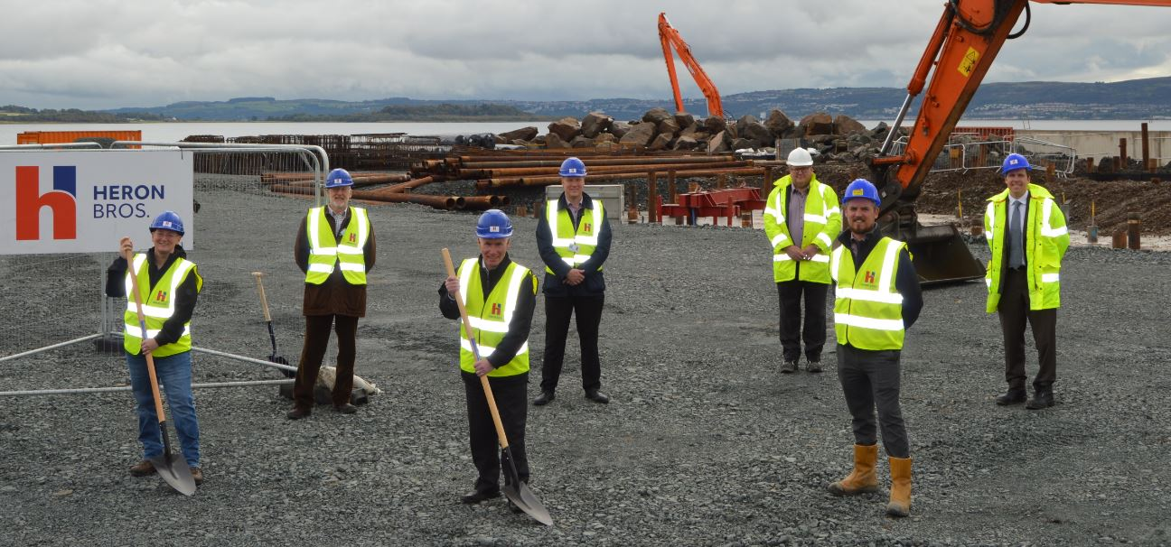Helensburgh Waterfront Development Topping Out Ceremony. 7 individuals in high-vis standing at Helensburgh Waterfront Development construction site with shovels.